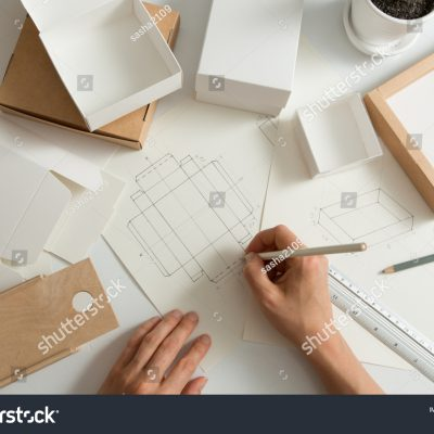 stock-photo-designer-draws-a-mockup-for-crafting-eco-cardboard-box-development-a-sketch-of-paper-packaging-1495175648