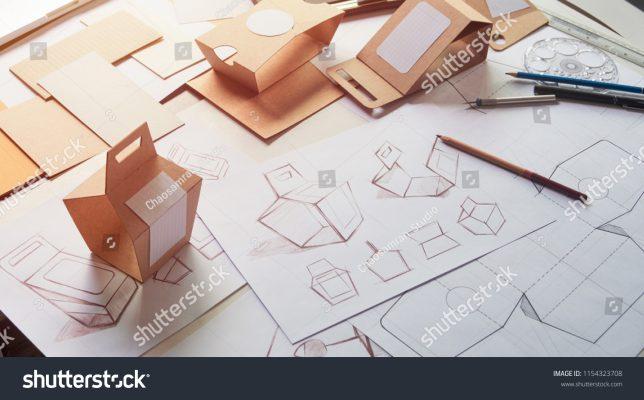 stock-photo-designer-sketching-drawing-design-brown-craft-cardboard-paper-product-eco-packaging-mockup-box-1154323708